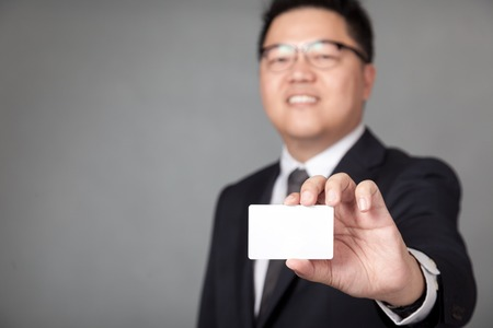 Asian businessman show a white card on gray background photo
