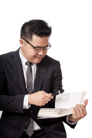 Asian businessman reading a book through magnifying glass  isolated on white background photo