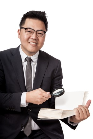 Asian businessman with book and magnifying glass smiling look at camera  isolated on white background photo