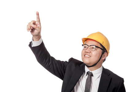Asian businessman with yellow hardhat point up and smile isolated on white background photo