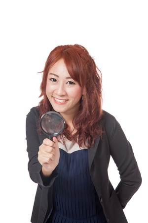 Asian office girl hold magnifying glass in front of her and smile isolated on white  Stock Photo - 28012360