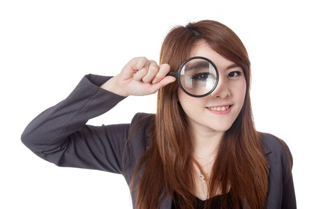Asian businesswoman look through magnifying glass and smile isolated on whtie background photo