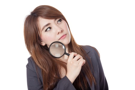 Asian businesswoman is  thinking with magnifying glass looking up isloate on white background Stock Photo - 28012380