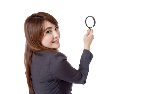 Asian businesswoman use magnifying glass look back to camera isolated on white background Stock Photo - 28012383