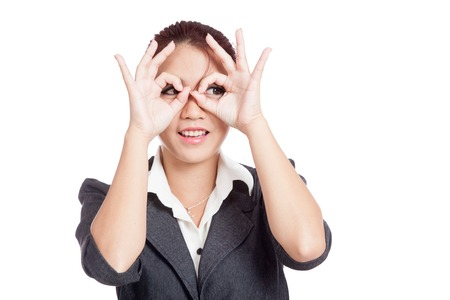 Asian business woman do funny  double OK sign as glasses isolated on white background photo