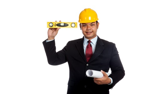 Asian engineer man  hold blue print and level look at camera and smile isolated on whtie background photo