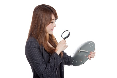 Asian Businesswoman look at a clock with magnifying glass  isolated on white background photo
