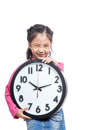Asian little girl hold a clock and laughing isolated on white background Banco de Imagens