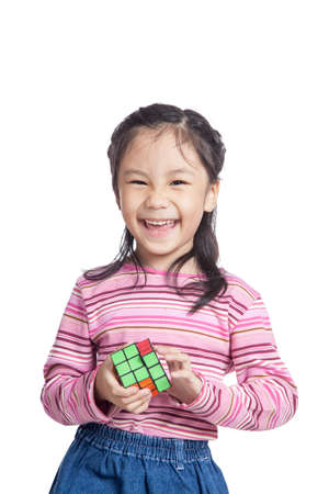 rubik: Asian little girl solve puzzle and laughing isolated on white background Stock Photo