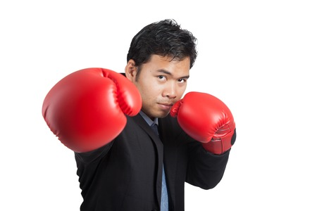 Asian businessman punch with red  boxing glove isolated on white background photo