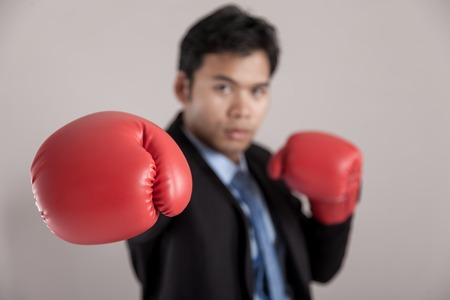 Asian businessman punch with red  boxing glove focus at the glove on gray background photo