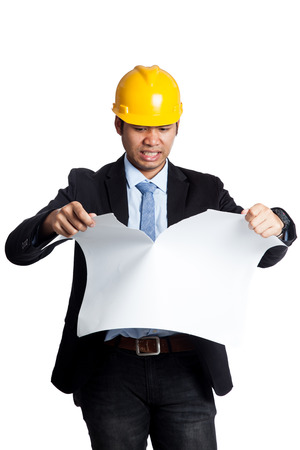 Angry Asian engineer man tearing a plan isolated on white background photo