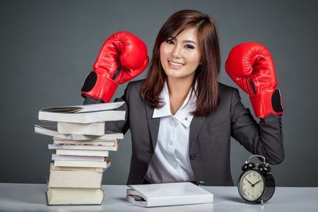 Asian businesswoman ready to fight with boxing glove books and clock on gray background photo