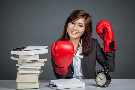 Asian businesswoman ready for hard work  with boxing glove books and clock on gray background