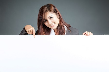 Asian businesswoman stand behind a blank billboard , point down and smile on gray background