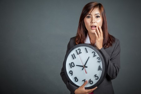 Asian businesswoman surprised hold a clock on gray background Foto de archivo