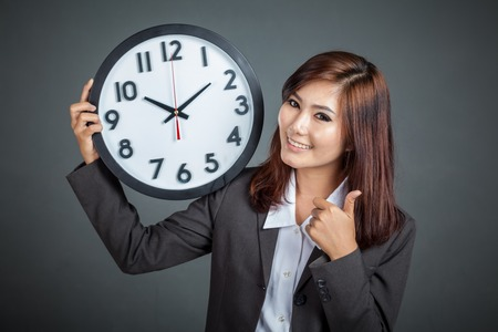 Asian businesswoman hold a clock thumbs up and smile on gray background Foto de archivo