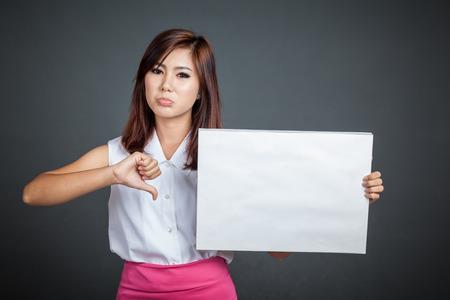 fille triste: Fille asiatique tenir les pouces de signe et de montrer vides vers le bas sur fond gris Banque d'images