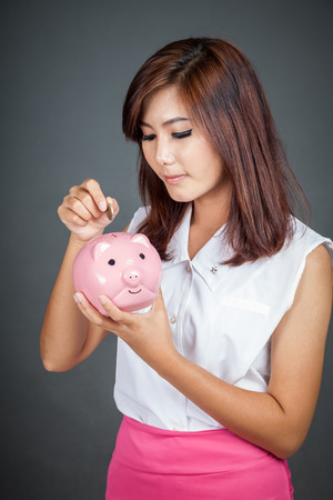 Beautiful Asian girl put a coin to pink pig money box on gray background photo