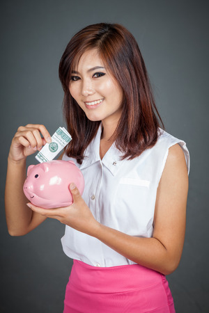 Beautiful Asian girl smile put a bill to pink pig money box on gray background photo