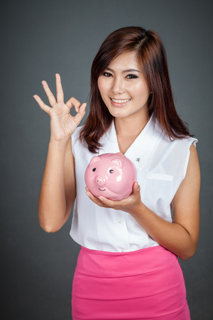 Beautiful Asian girl show OK sign with a pink pig money box on gray background photo