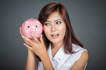 Beautiful Asian girl wonder how much money in pig money box shake it on her ear on gray background photo