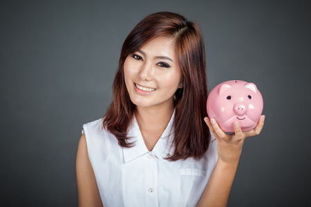 Beautiful Asian girl with a pink pig money box on gray background photo