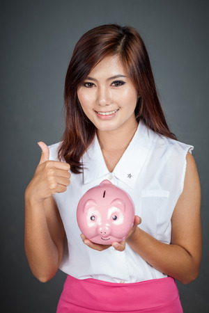 Beautiful Asian girl thumbs up with a pink pig money box on gray background photo