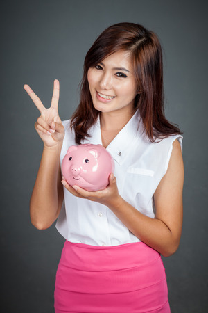 Beautiful Asian girl show victory sign with a pink pig money box on gray background photo