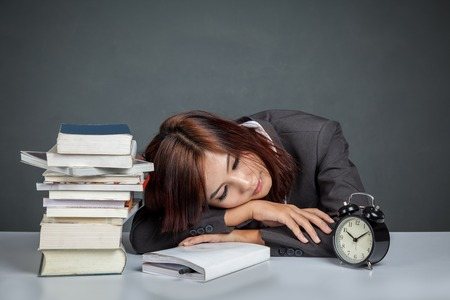 get tired: Asian businesswoman get tired reading many books on gray background Stock Photo