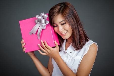 Beautiful Asian girl love a gift box on gray background photo