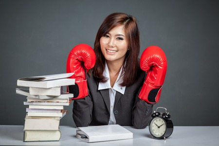 Asian businesswoman with boxing glove, books and clock on gray background photo
