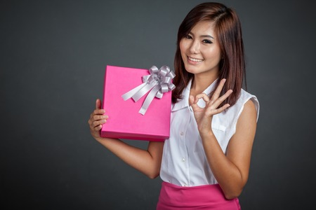 Beautiful Asian girl show OK with a gift box on gray background photo