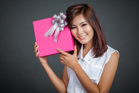 Beautiful Asian girl happy with a gift box on gray background photo