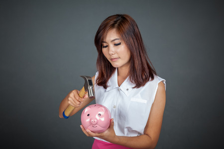 Beautiful Asian girl about to hit money box with hammer on gray background photo