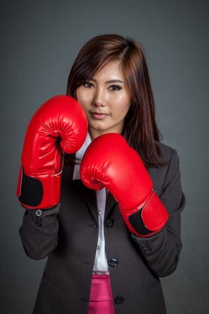Asian businesswoman guard with boxing glove on gray background photo