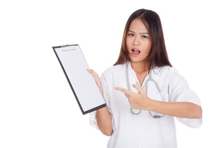 Angry Asian young female doctor point to blank clipboard  isolated on white background photo