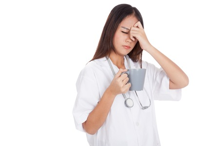 Asian young female doctor got headache with a cup of coffee  isolated on white background photo