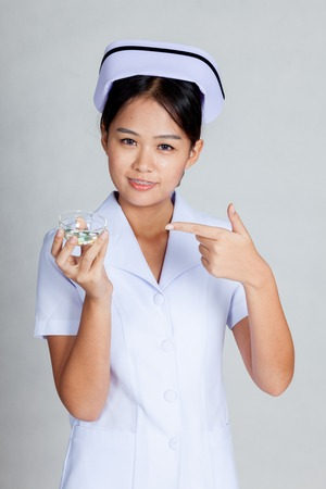 Young Asian nurse point at pills on gray background photo