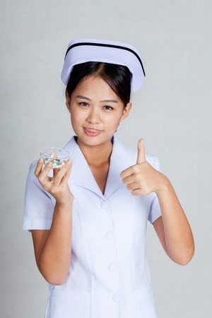 Young Asian nurse show thumbs up with some pills on gray background photo