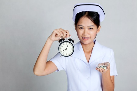 Young Asian nurse with clock and pills on her palm hand on gray background photo