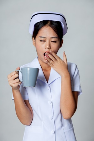 Young Asian nurse yawn with a cup of coffee on gray background photo