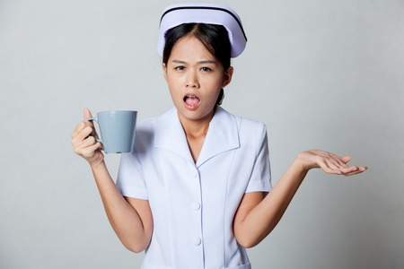 Angry young Asian nurse on gray background photo