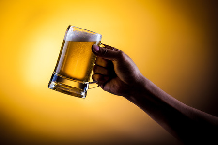 Hand hold mug of beer on gold background 스톡 콘텐츠