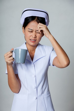 Young Asian nurse got headache with a cup of coffee on gray background photo