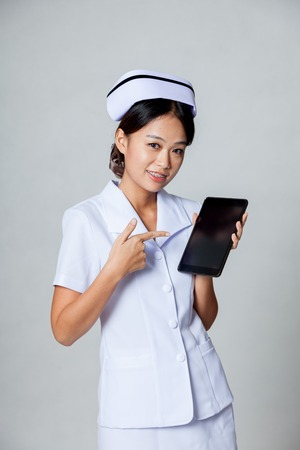 Young Asian nurse point to a tablet pc on gray background photo