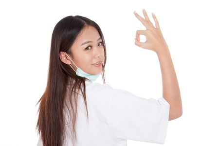 Young Asian female doctor  turn back show OK sign  isolated on white background photo