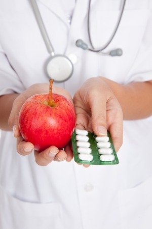 Close up of doctor hold pills and apple photo