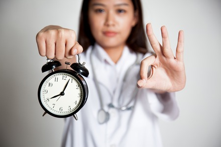 Young Asian female doctor show OK with a clock focus at the clock on gray background photo