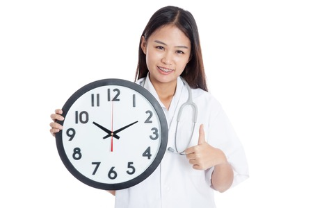 Young Asian female doctor thumbs up with a clock  isolated on white background photo
